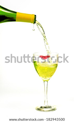 Wine bottle pouring into a crystal glass with a lipstick imprint on its rim. - stock photo