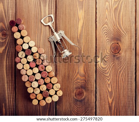 Wine bottle shaped corks and corkscrew over rustic wooden table background. View from above with copy space - stock photo