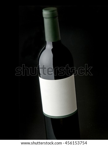 Wine bottle shot against black background with blank label - stock photo