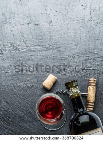 Wine bottle, wine glass and corkscrew on the graphite board. - stock photo