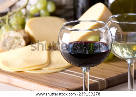 Wine bottle with a glass of red wine with cheese and grapes - stock photo