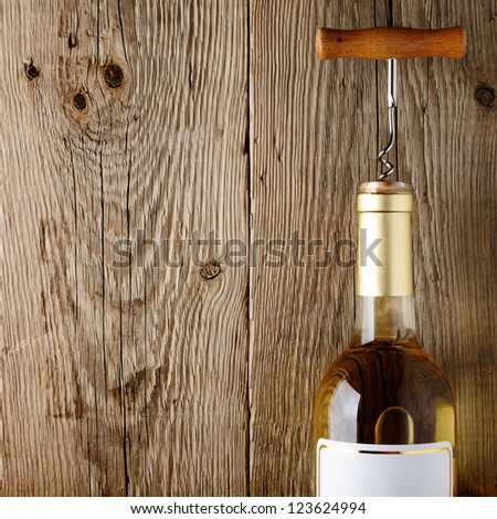 Wine bottle with corkscrew on wooden background - stock photo