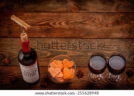 Wine bottle with self made label  and glasses filled with wine on wooden table  - stock photo