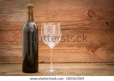 Wine bottle with the label removed standing alongside an elegant wineglass against rustic wooden boards with copy space - stock photo