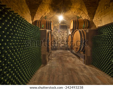 wine bottles and barrels in winery cellar of Tuscany, Italy - stock photo