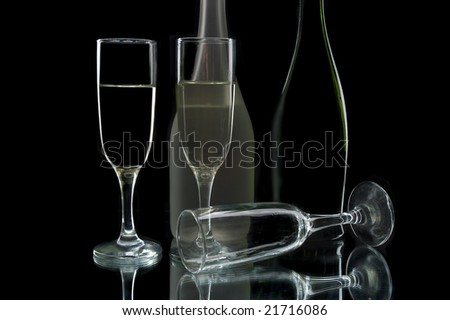 Wine bottles and glasses against a black background - stock photo