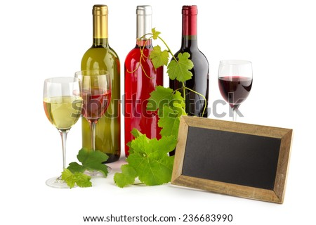 wine bottles and glasses, blackboard and grapevine - stock photo