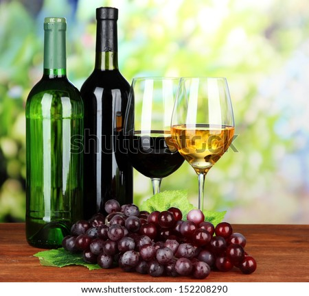 Wine bottles and glasses of wine on bright background - stock photo