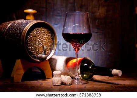 Wine bottles and small barrel with glass on old wooden background - stock photo