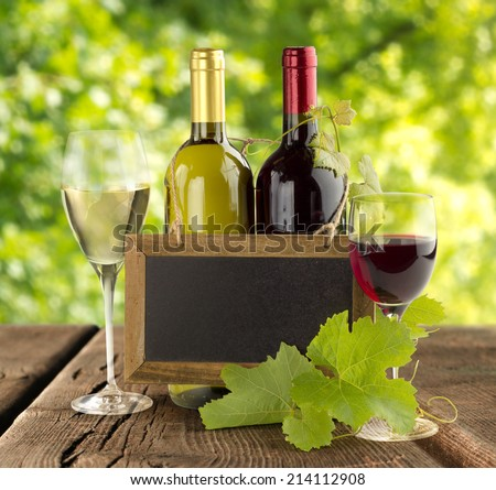 wine bottles and small blackboard on wooden table