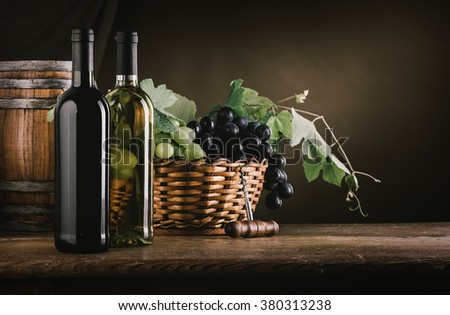 Wine bottles, barrel and grapes in a basket on a wooden table, wine tasting still life - stock photo