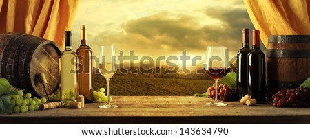 Wine bottles, barrels and vineyard in sunset - stock photo