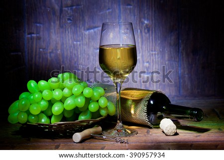 Wine bottles, bunch of grapes and glass of white wine on blue old wooden background - stock photo