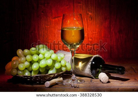 Wine bottles, bunch of grapes and glass of white wine on red old wooden background - stock photo