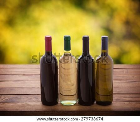 Wine bottles close up on wooden desk. Flat mock up for design. Blurred background. - stock photo