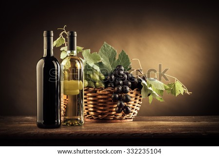 Wine bottles, grapes and vine leaves in a basket on a rustic wooden table, still life - stock photo