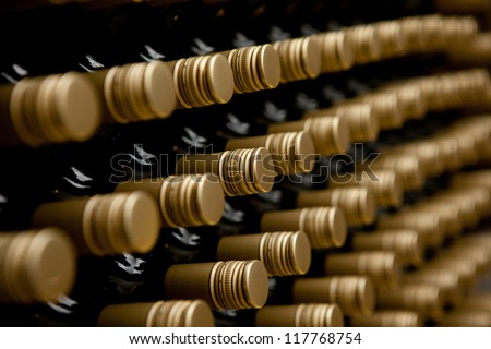 Wine bottles in a row. tops of alcohol in winery or cellar