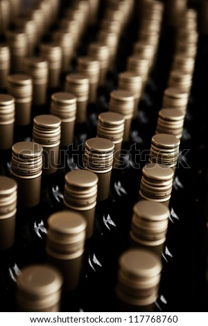 Wine bottles in a row. tops of alcohol in winery or cellar - stock photo
