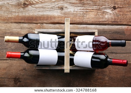 Wine bottles in basket on wooden background - stock photo