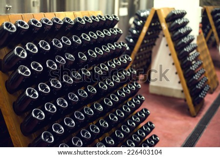 wine bottles in wine cellar. Selective focus. - stock photo