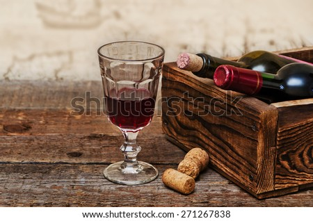 Wine bottles in wooden boxes, crystal glass with red wine are on the wooden background - stock photo