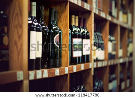 Wine bottles on wooden shelf in wine store - stock photo