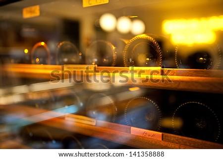 Wine Bottles rack. Glassy wine rack in the french restaurant - stock photo