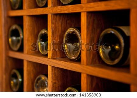 Wine Bottles rack. Wooden wine rack in the french restaurant - stock photo