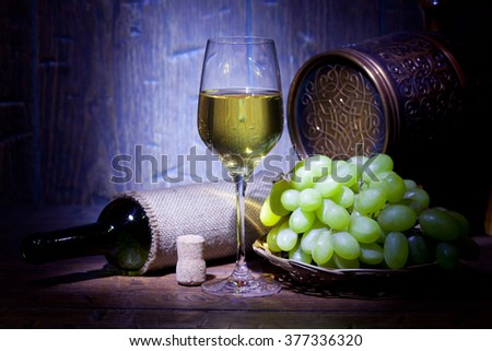 Wine bottles, small barrel,  bunch of grapes and with glass of white wine on blue old wooden background - stock photo