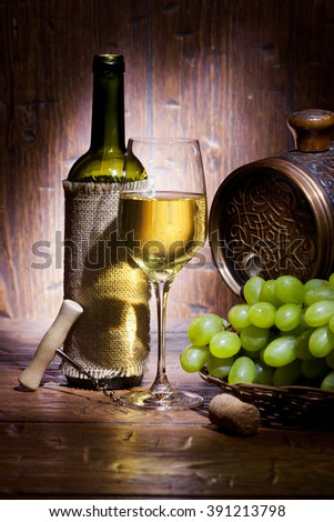 Wine bottles, small barrel,  bunch of grapes and with glass of white wine on old wooden background - stock photo