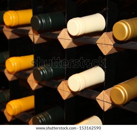 wine bottles stacked on wooden racks. Shallow depth of field - stock photo