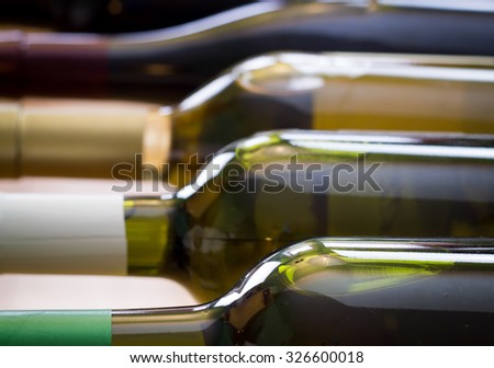 Wine bottles stacked on wooden racks shot with limited depth of field - stock photo