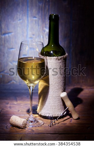 Wine bottles with glass of white wine on blue old wooden background - stock photo