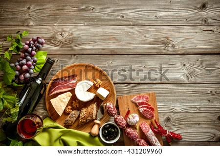 Wine bottles with grapes, cheese and traditional sausages on wooden background with copy space - stock photo