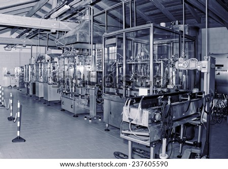 Wine bottling equipment line in a hangar, toned image - stock photo