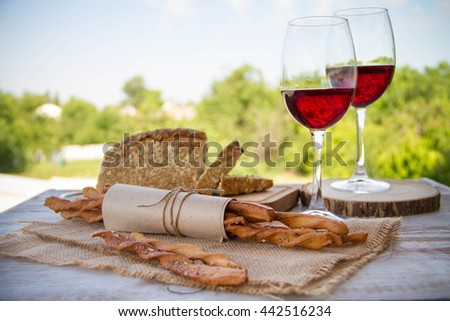 Wine, bread and wheat on the wooden table