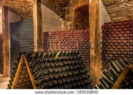 Wine cellar, a row of champagne bottles Bottles of wine stocked in a wine cellar. - stock photo