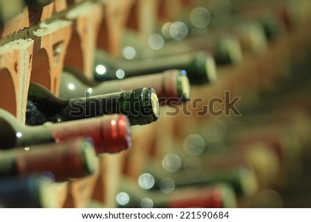 Wine cellar bottles rows covered with dust macro - stock photo
