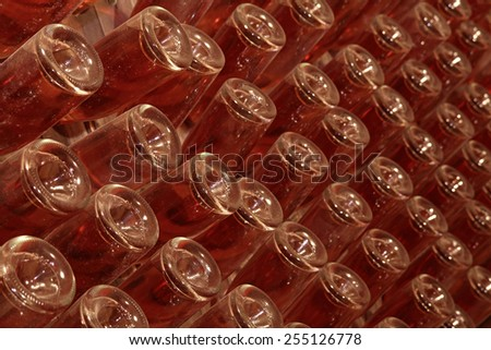 Wine cellar red bottles background; nice light effect on the glass. - stock photo