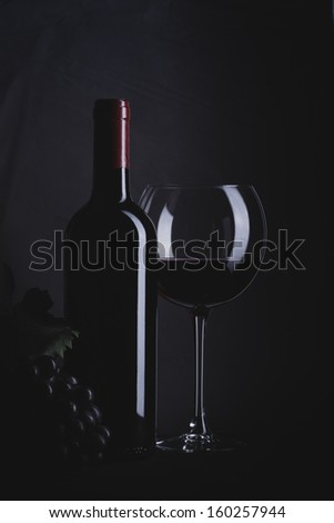 Wine Concept. Bottle of wine with glass and grapes on white desk over black background. - stock photo