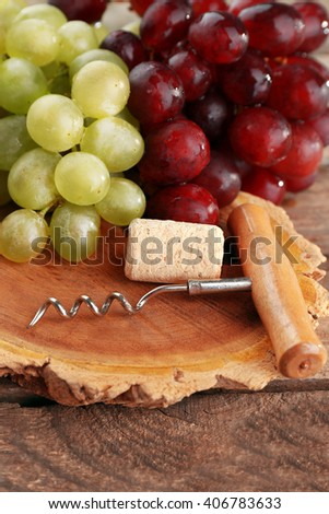 Wine cork and tailspin with bunch of grapes on wooden background
