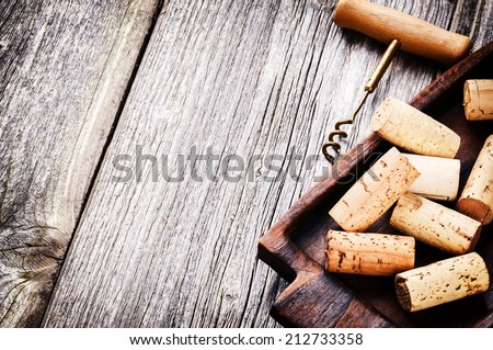 Wine corks and corkscrew on wooden table - stock photo