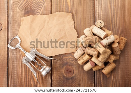 Wine corks and corkscrew over rustic wooden table background. View from above with piece of paper for copy space - stock photo