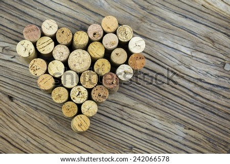 Wine corks form a heart shape image on the wood board background - stock photo
