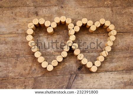 Wine corks form a heart shape on the wood board - stock photo
