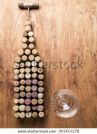 Wine corks in the shape of wine bottle on the wooden background. - stock photo