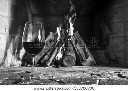 Wine cup and fire place on the background. - stock photo