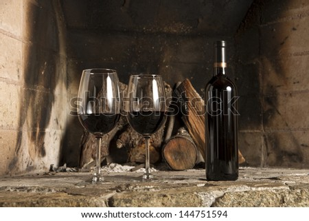 Wine cup, bottle grapes and cork over a wooden table. - stock photo