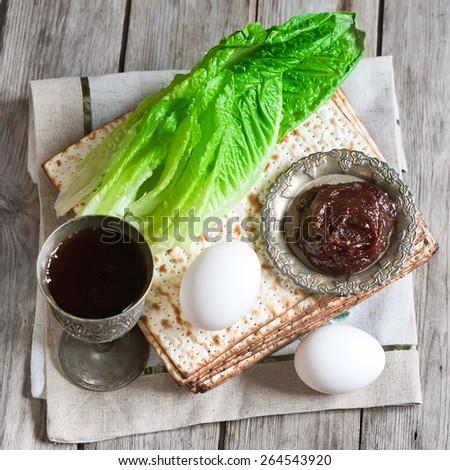 Wine, egg, bitter salad leaves, matzot and haroset - traditional jewish passover celebration elements. - stock photo