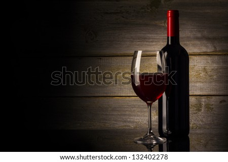 Wine glass and Bottle on a wooden background - stock photo